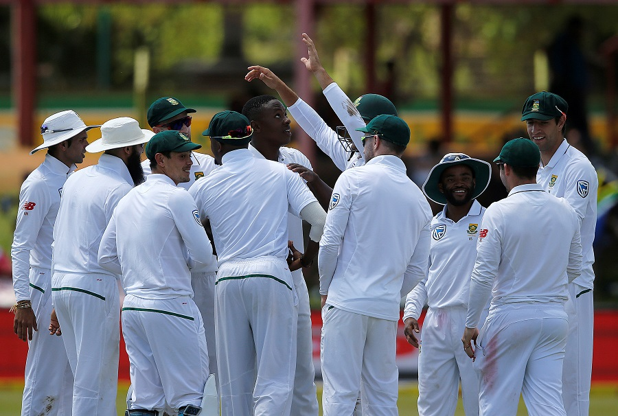 South Africa's bowler Kagiso Rabada (C) is congratulated by teammates after taking his 100th Test match wicket during the third day of the second Test cricket match between South Africa and Bangladesh in Bloemfontein on October 8, 2017.  / AFP PHOTO / MARCO LONGARI