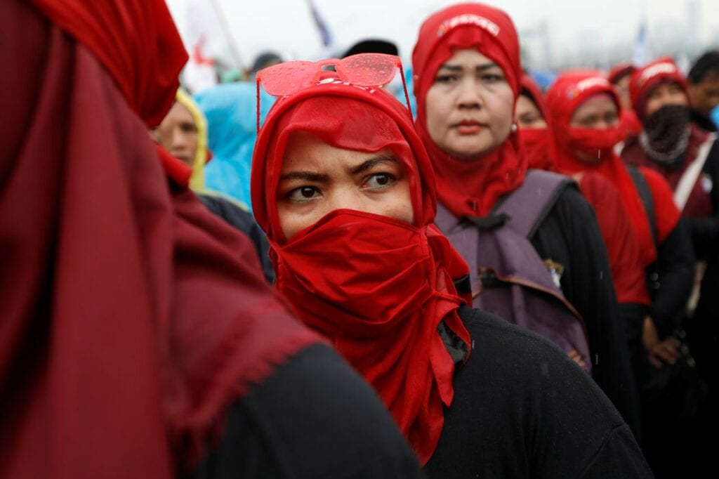 JAKARTA A labourer looks on as she takes part in a protest outside Indonesia's parliament building in favour of their demands.