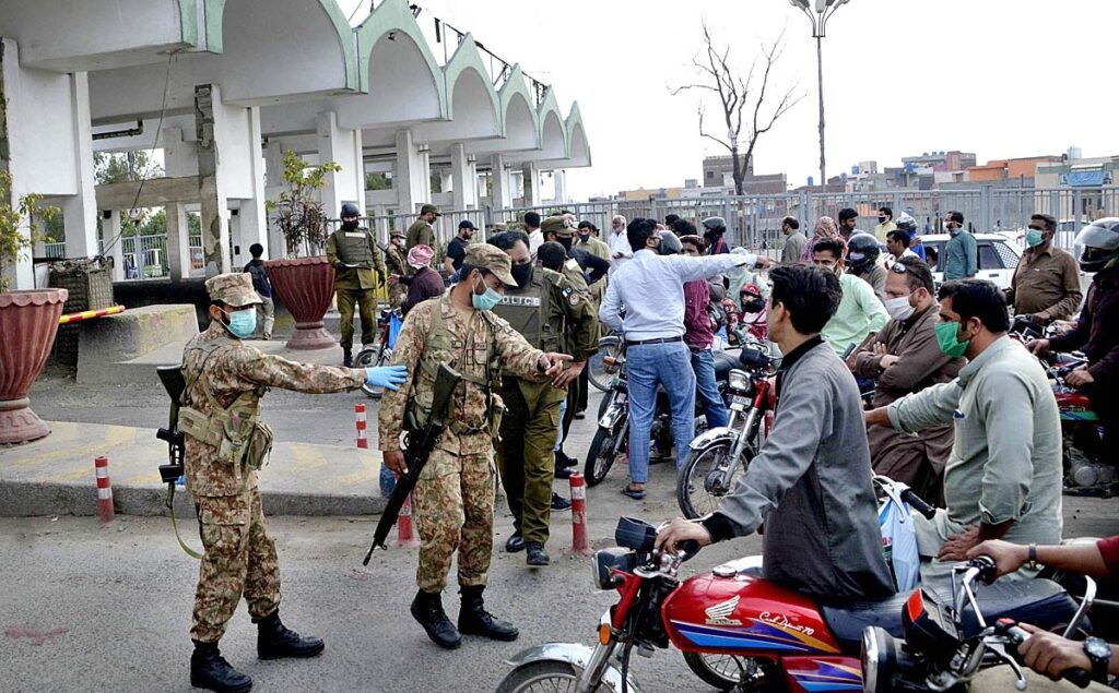 APP45-26 LAHORE: March 26 - Pak Army and Police officials stops vehicles for unnecessary go out as Punjab Government announce lockdown for 15 days in province for precautionary measures to prevent corona virus. APP Photo by Mustafa Lashari